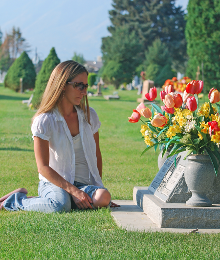Woman Sitting Near Headstone In Cemetery